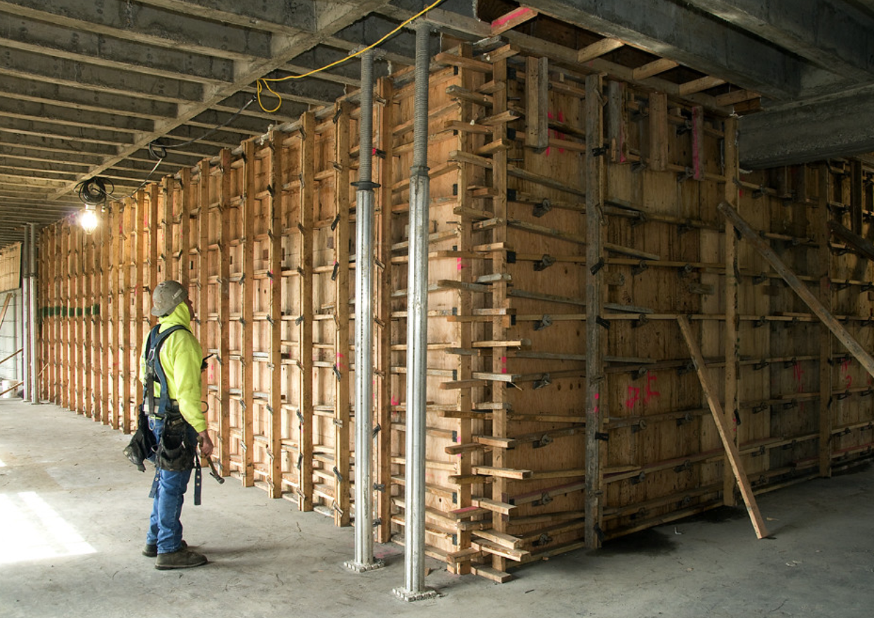 A construction worker inspects the frames for new shear walls that will give added structural support to the building.